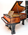 The Golden Age of Pianos Exhibition. The Peter Behrens Schiedmayer grand piano with an Art-Deco case inlaid with mother of pearl, lapis lazuli and malachite in geometric designs. The lid design resembles an angels wing. Music desk made from brass with a sunburst design.