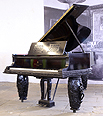 The Golden Age of Pianos Exhibition. A Steinway model B grand piano with an ebonised case. Case features three tiered mouldings at base. Music desk has a geometric filigree design. Piano has three barrel legs each carved with figures playing musical instruments and floral relief detail. Designed by Oskar Kaufmann