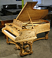 The Golden Age of Pianos Exhibition. An intricately carved Bechstein Model C grand piano with an ornately carved, walnut case. Cabinet features carvings of two swans on the water on piano cheeks. Twisted around the rear piano leg is a two-headed serpent dragon. Professor Max Koch created the design for this Bechstein based on themes found in Richard Wagner's great Ring Cycle works.
